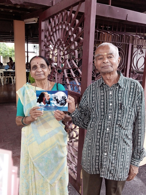 An elderly couple at the temple pose for the camera after receiving the message of Kalki Avatar Ra Gohar Shahi.